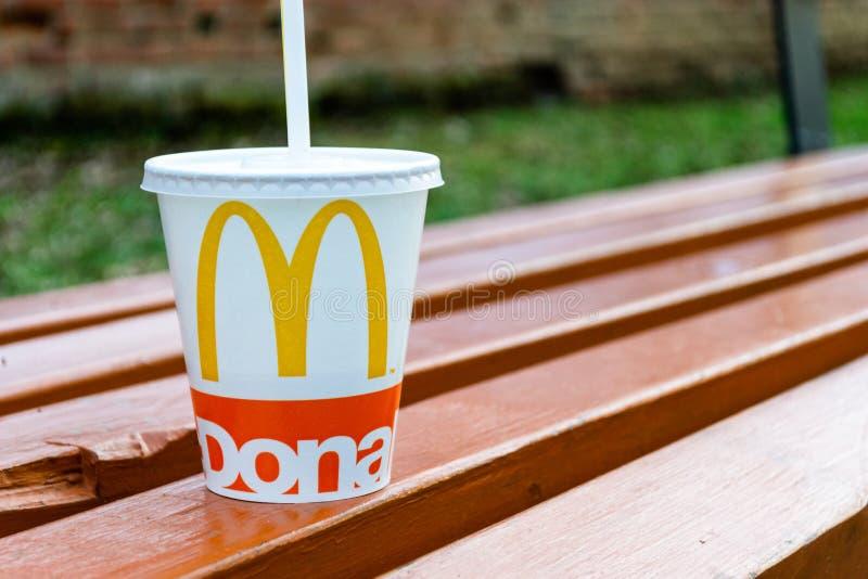 Tazza di McDonalds abbandonata su un banco di parco, con il coperchio sopra e una paglia bianca fotografie stock