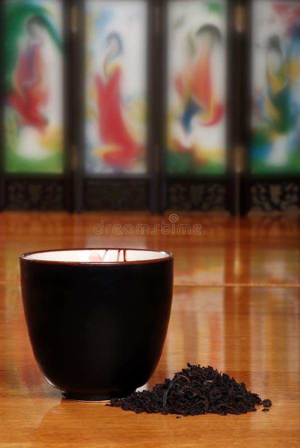 Tazza di tè asiatica con i fogli dell'erba fotografia stock libera da diritti