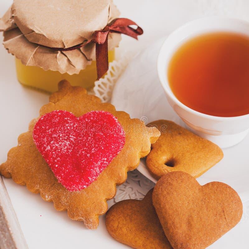 Tazza di tè con i biscotti a forma di del cuore Biscotti di rosso dello zucchero Un quadrato, lati uguali Instaphoto con i filtri fotografie stock libere da diritti