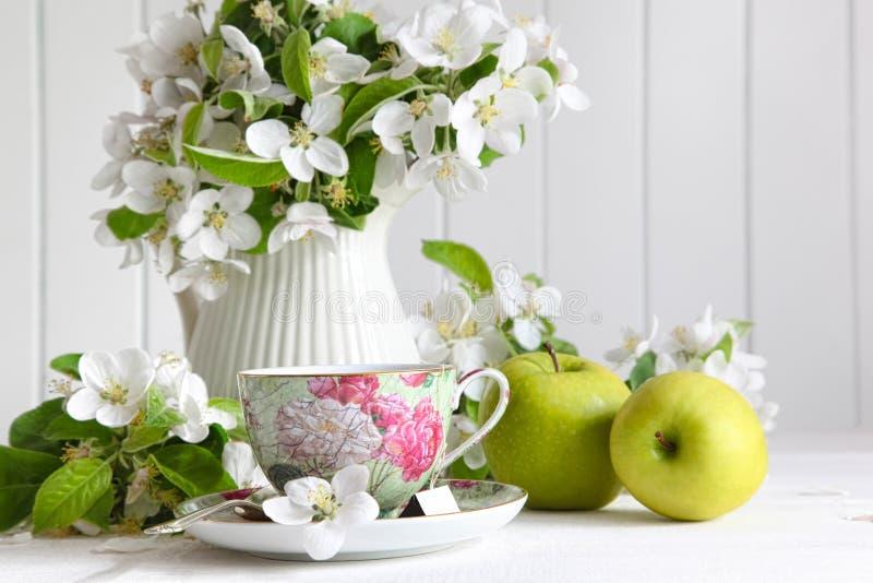Tazza di tè con i fiori del fiore e le mele verdi fotografia stock