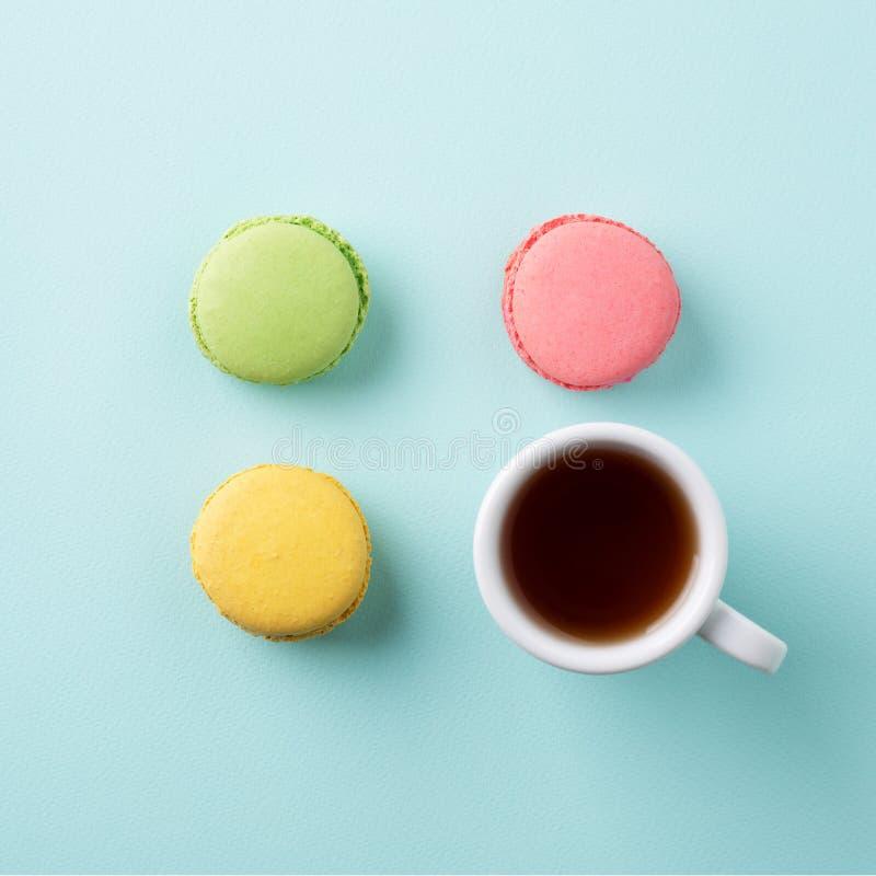 Tazza di tè con i macarons variopinti su fondo blu-chiaro fotografia stock