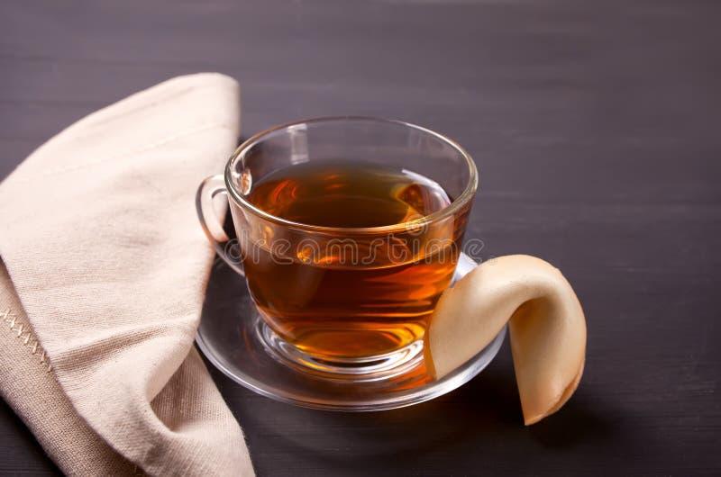 Tazza di tè con il biscotto di fortuna su un fondo di legno fotografie stock