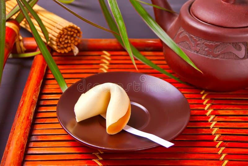 Tazza di tè con il biscotto di fortuna, teiera nello stile orientale su un vassoio di legno immagine stock libera da diritti