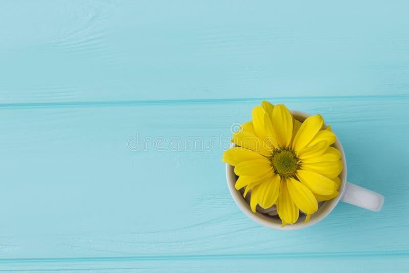 Tazza di tè con il fiore giallo fotografie stock