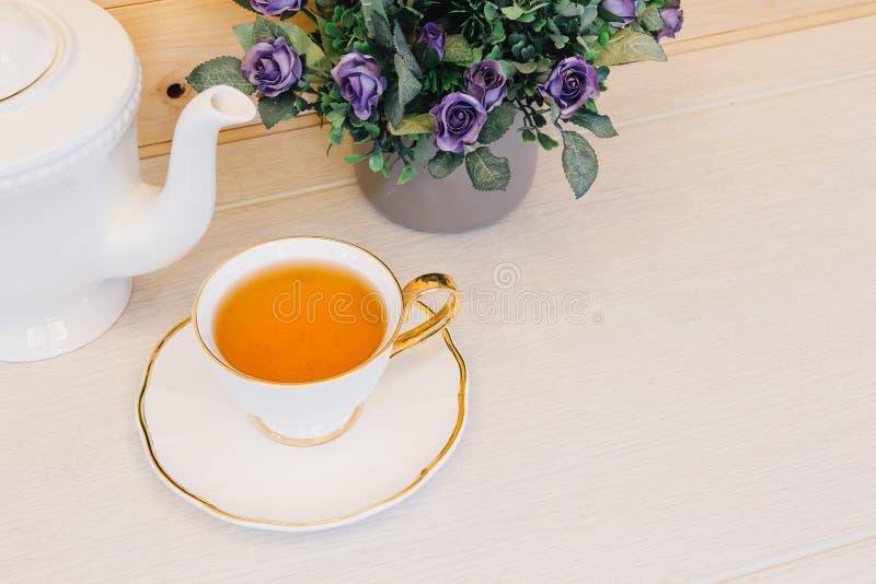 Tazza di tè con il fiore su una vista superiore del fondo di legno fotografie stock libere da diritti