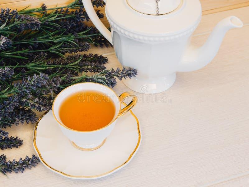 Tazza di tè con il fiore su una vista superiore del fondo di legno immagini stock libere da diritti