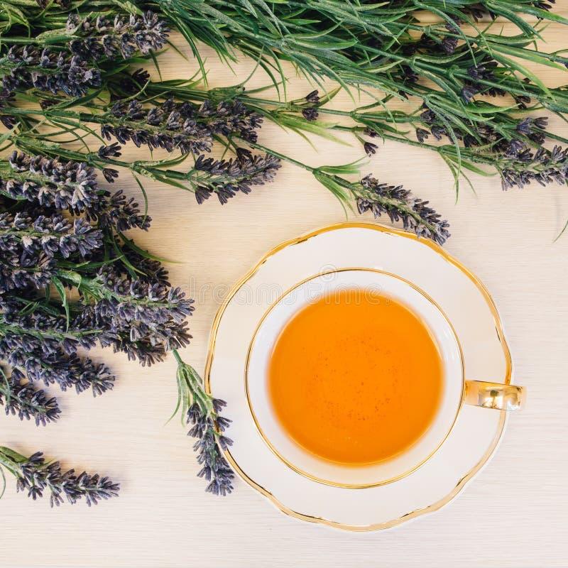 Tazza di tè con il fiore su una vista superiore del fondo di legno fotografia stock libera da diritti