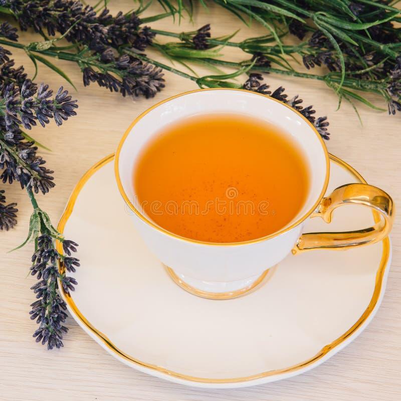 Tazza di tè con il fiore su una vista superiore del fondo di legno fotografie stock