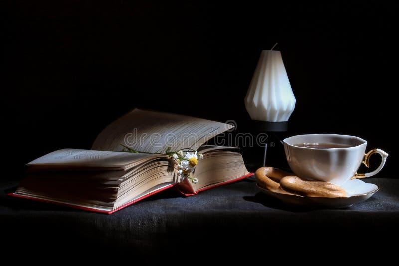 Tazza di tè con il libro aperto e la fine della candela su, fondo nero Concetto di autunno Immagine della carta da parati immagini stock libere da diritti