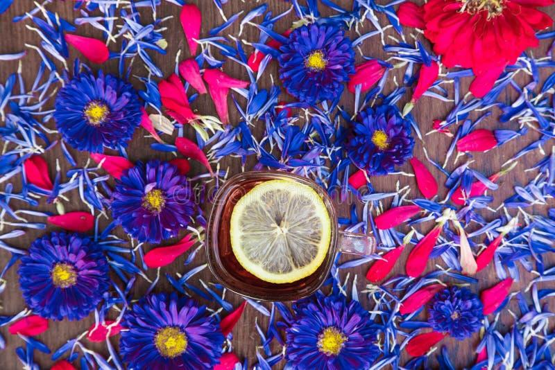 Tazza di tè con il limone con i fiori blu fotografia stock