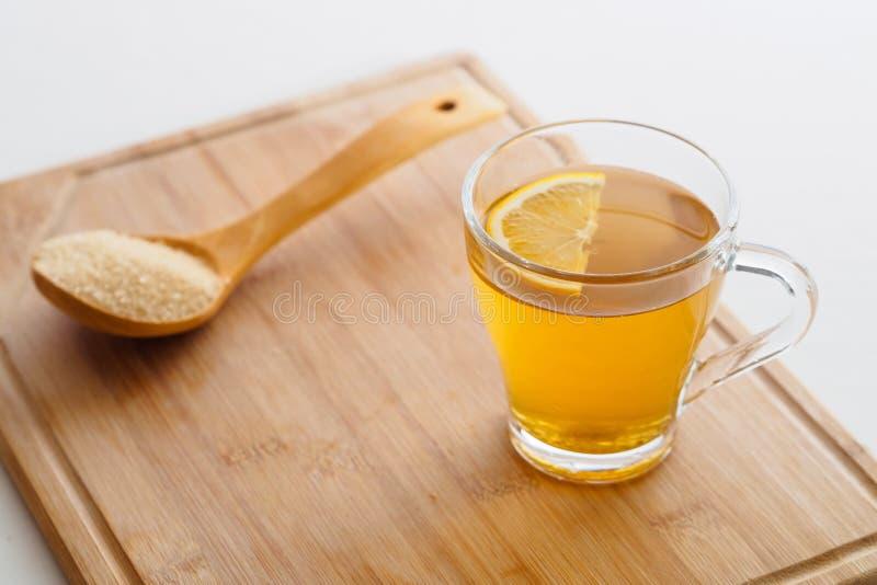 Tazza di tè con il limone ed il cucchiaio di legno fotografia stock
