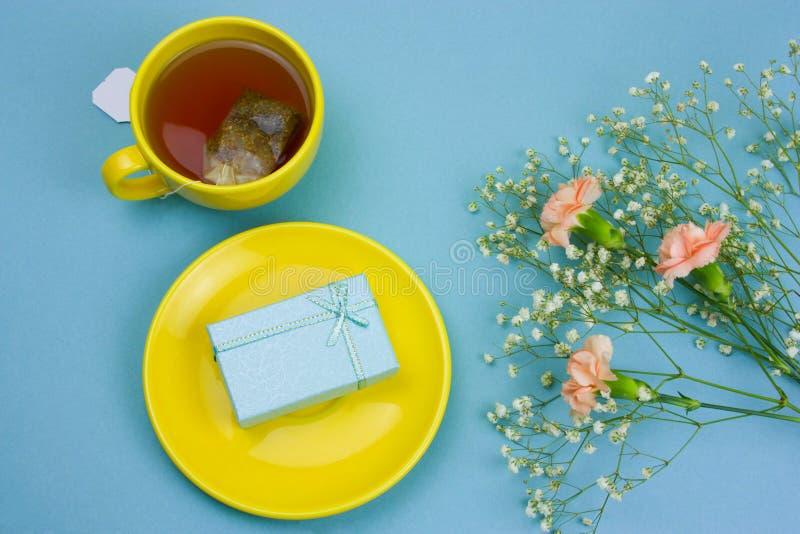 tazza di tè con la bustina di tè, contenitore di regalo su un piatto e mazzo dei fiori su un fondo blu pastello fotografie stock