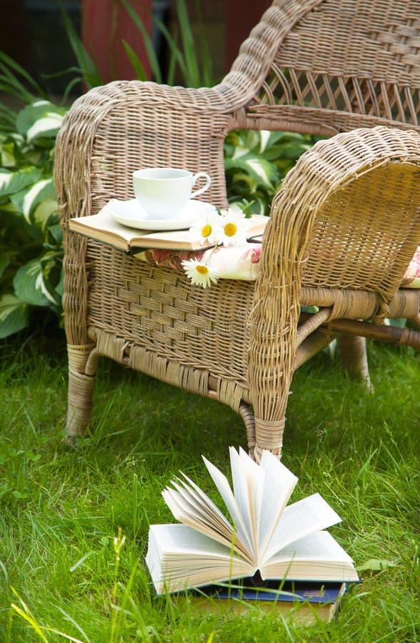 Tazza di tè con libri e camomille su una sedia fotografie stock