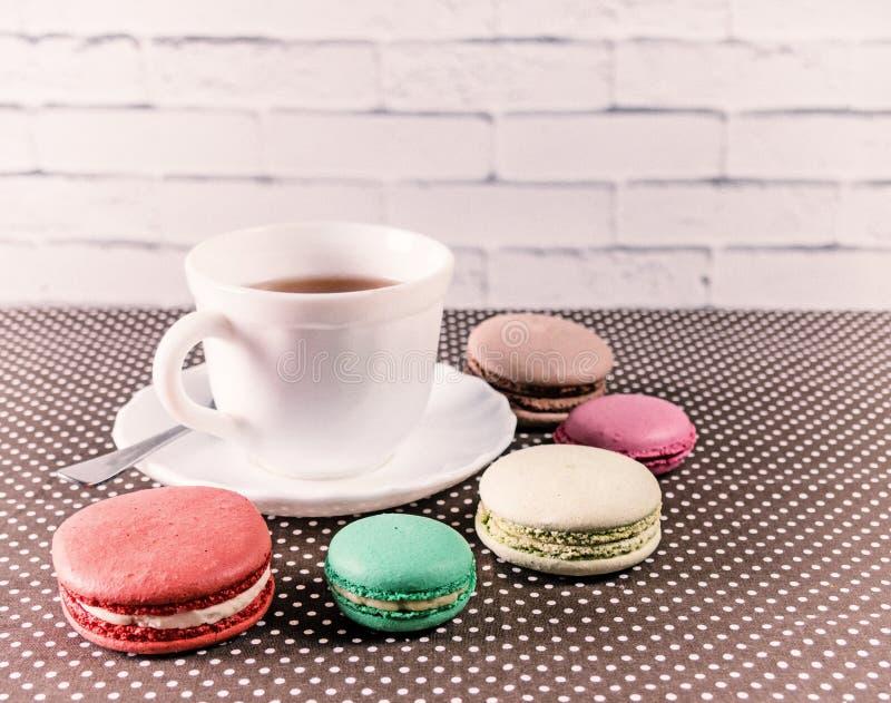 Tazza di tè con macaron francese variopinto immagine stock