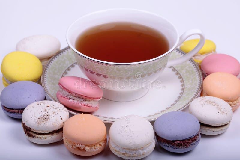 Tazza di tè con macaron francese variopinto fotografia stock