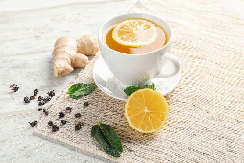 Tazza di tè delizioso con la menta, il limone e lo zenzero sulla tavola fotografia stock