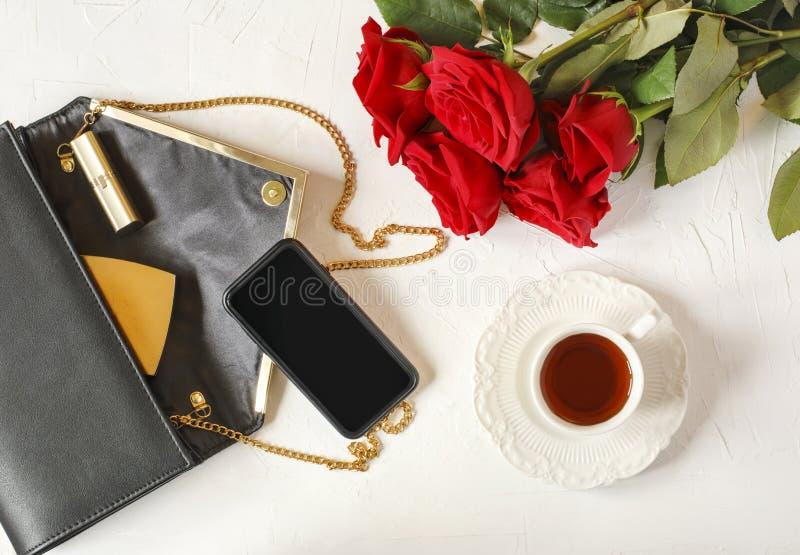 Tazza di tè, della borsa del ` s della donna e delle rose rosse su fondo bianco piano fotografia stock libera da diritti
