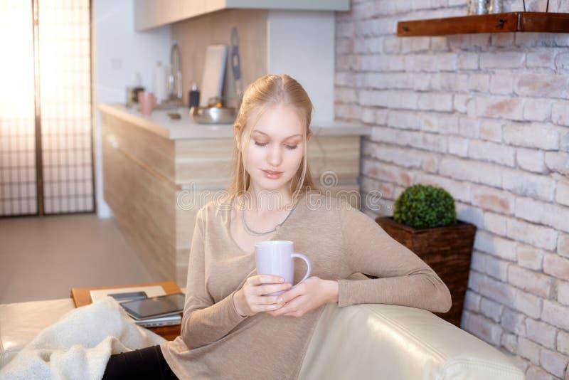 Tazza di tè della tenuta della giovane donna a casa immagine stock libera da diritti