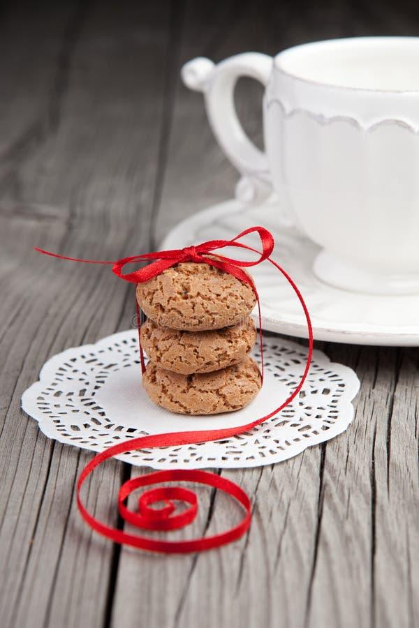 Tazza di tè e dei biscotti su fondo di legno immagini stock