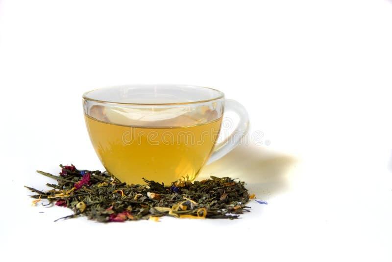 Tazza di tè e di tè sciolto su un fondo bianco fotografia stock