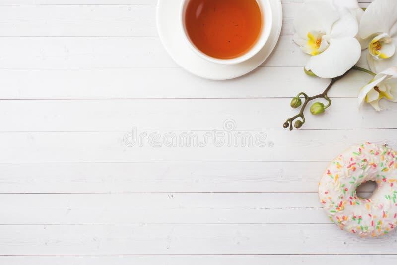Tazza di tè e guarnizioni di gomma piuma, orchidea bianca sulla tavola bianca con lo spazio della copia Disposizione piana, vista fotografia stock libera da diritti