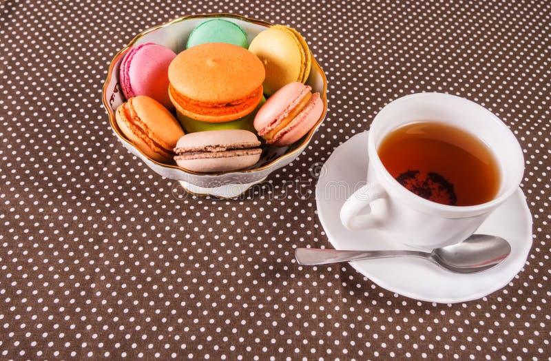 Tazza di tè e un piatto con i maccheroni francesi variopinti su una tavola con lo spazio della copia immagini stock libere da diritti