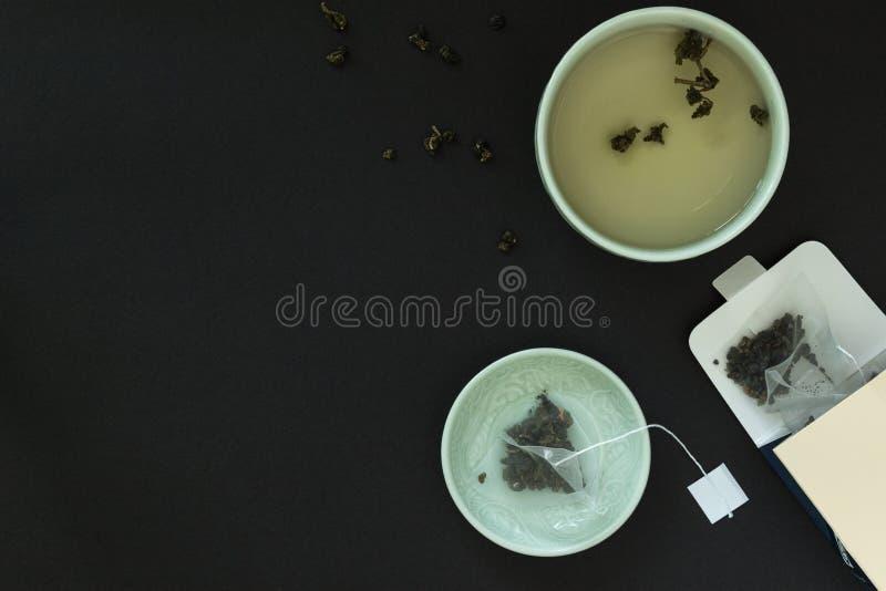 Tazza di tè giapponese, piattino con una borsa delle foglie di tè e cartone immagini stock