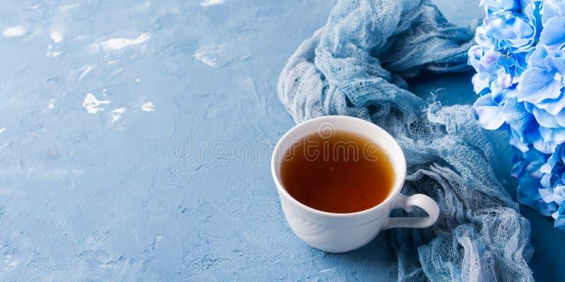Tazza di tè su fondo blu con i fiori immagini stock libere da diritti