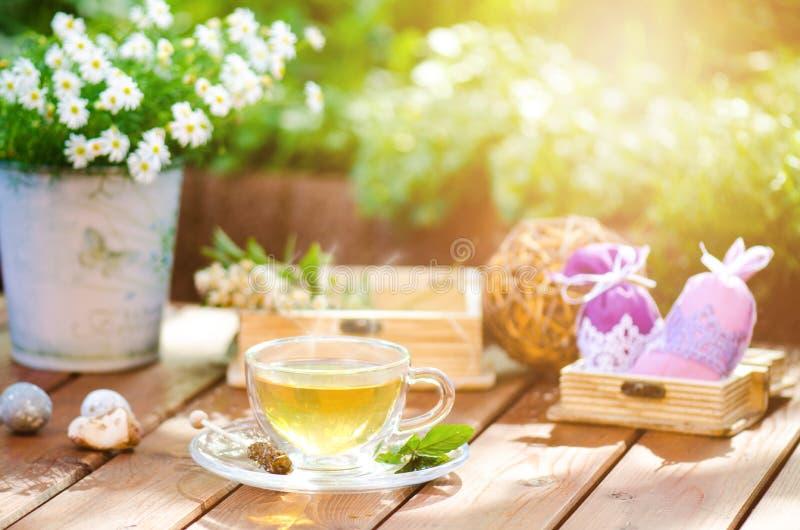 Tazza di tè su un cosist dello sfondo naturale dei fiori immagini stock libere da diritti