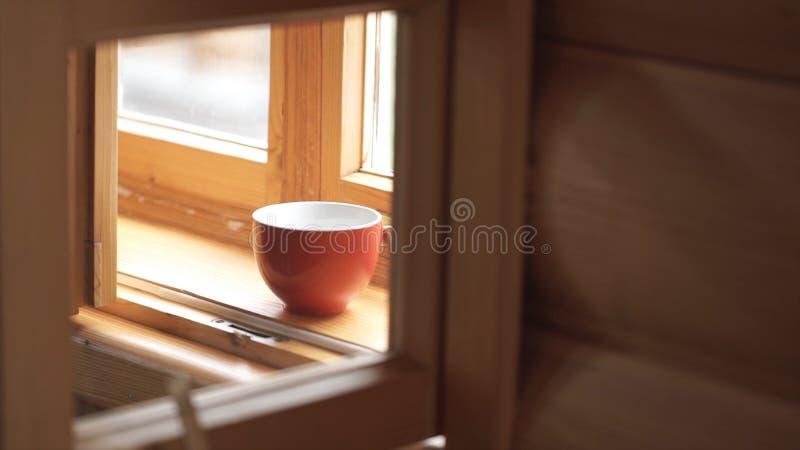 Tazza di tè su un davanzale di legno della finestra Tazza di tè su un davanzale di legno Freni il tempo con una tazza della vista fotografia stock libera da diritti