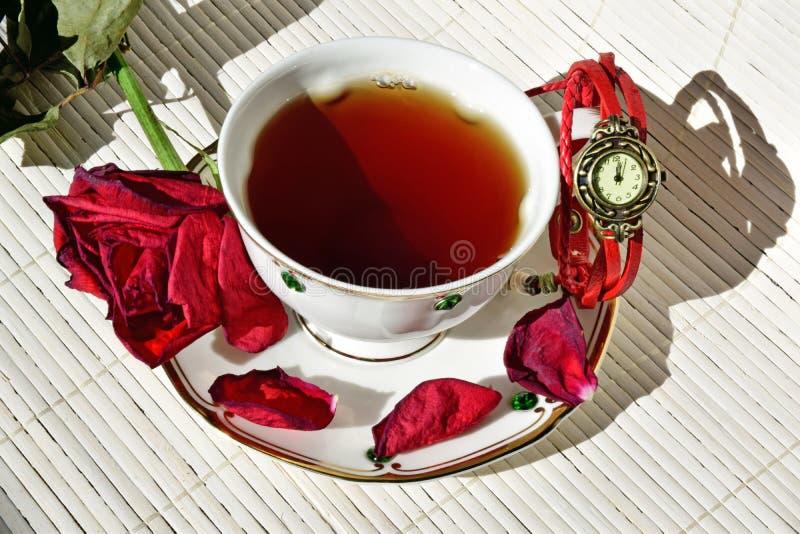 Tazza di tè Sul piattino sono i petali rosa asciutti sparsi fotografia stock libera da diritti