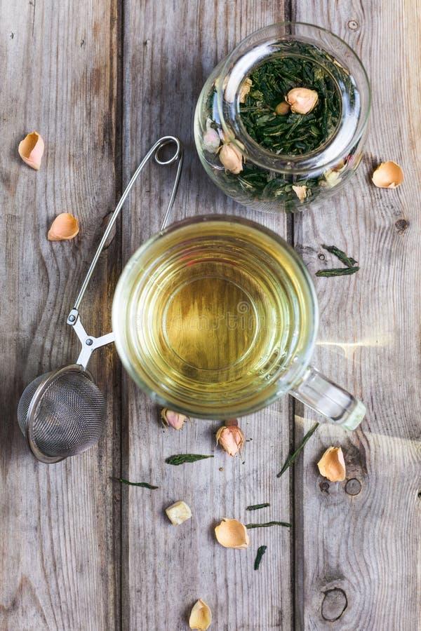Tazza di tè verde aromatizzato con i germogli ed i petali rosa fotografia stock
