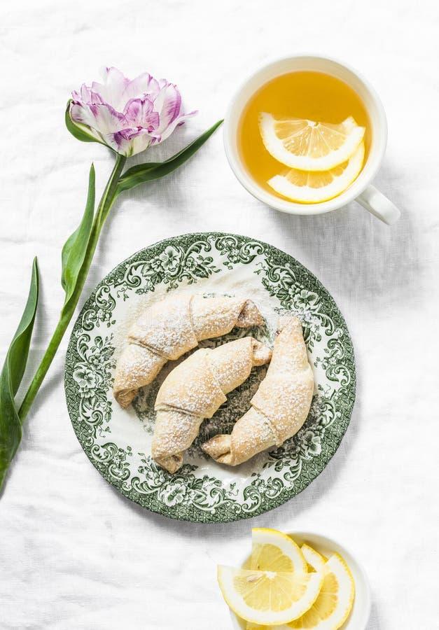 Tazza di tè verde con il limone, mini croissant, fiore del tulipano - natura morta accogliente di mattina su un fondo bianco, vis immagini stock libere da diritti
