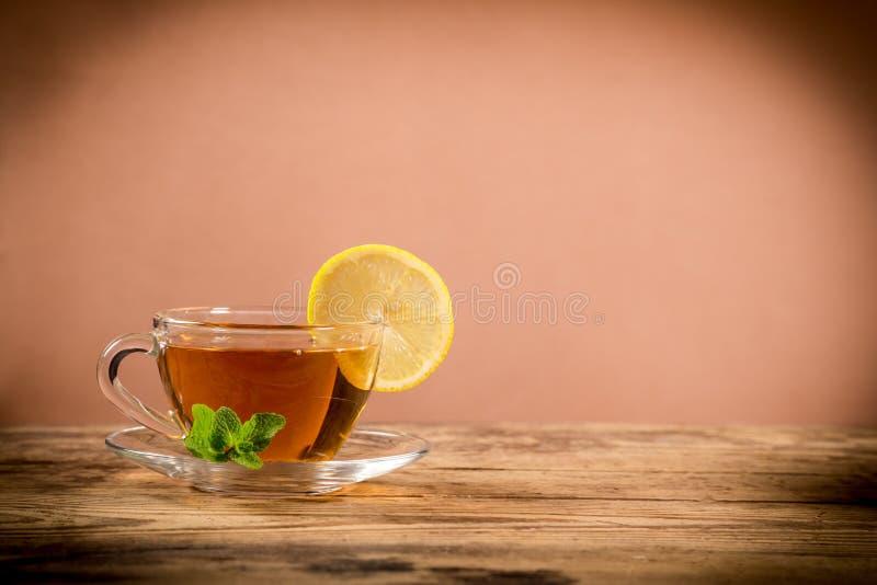 Tazza di tè verde con la foglia ed il limone della menta fotografia stock libera da diritti