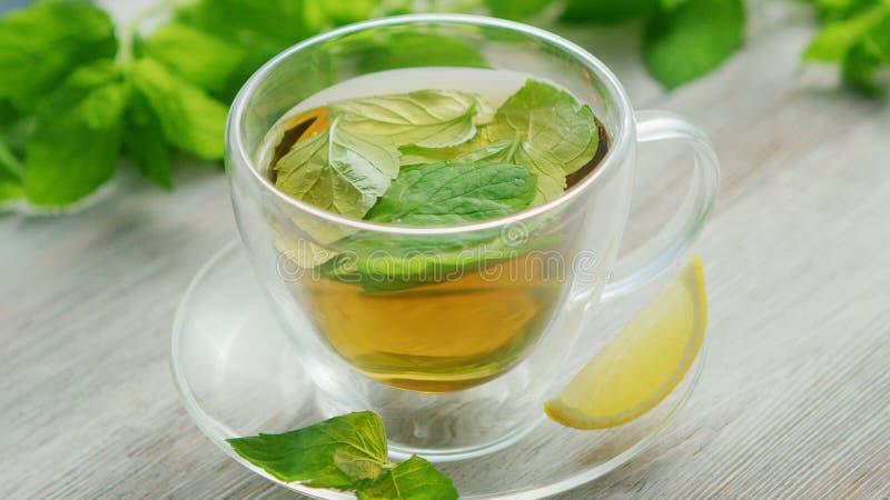 Tazza di tè verde con la menta ed il limone fotografie stock libere da diritti