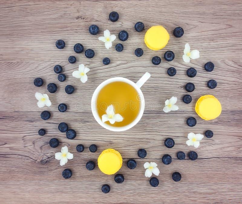 Tazza di tè verde, dei fiori e delle bacche caldi sulla tavola di legno Disposizione piana immagini stock