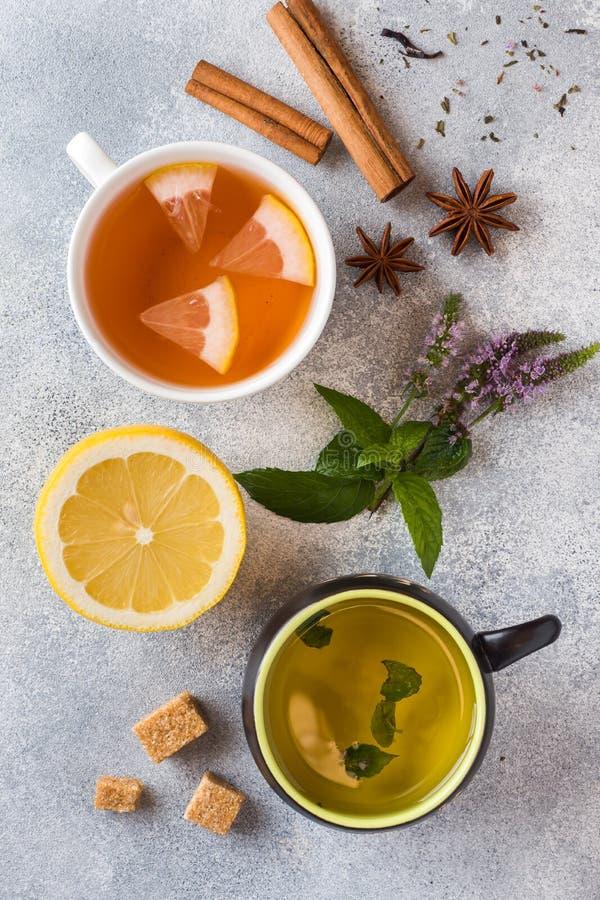 Tazza di tè verde e nera su una tavola, una menta e un limone, una cannella dello zucchero bruno e un anice grigi fotografia stock libera da diritti