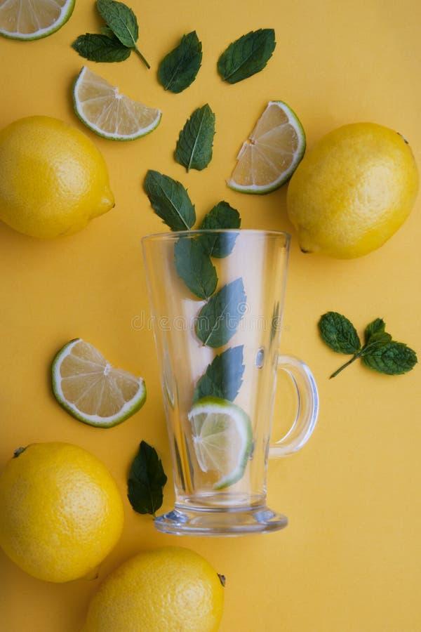 Tazza di tè di vetro vuota con le foglie di menta fresca, limone, agrume, calce, isolata sopra fondo giallo Autunno, bevanda sana immagine stock