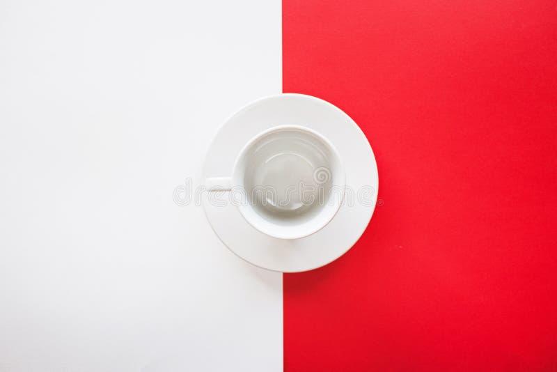 Tazza di tè vuota isolata su fondo rosso e bianco fotografia stock libera da diritti