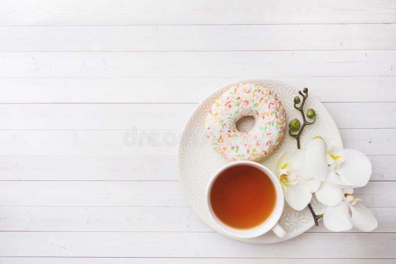 Tazza di t? e guarnizioni di gomma piuma, orchidea bianca sulla tavola bianca con lo spazio della copia Disposizione piana, vista fotografie stock
