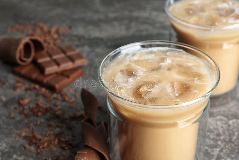 Tazza di vetro con caffè ghiacciato su grigio immagine stock libera da diritti