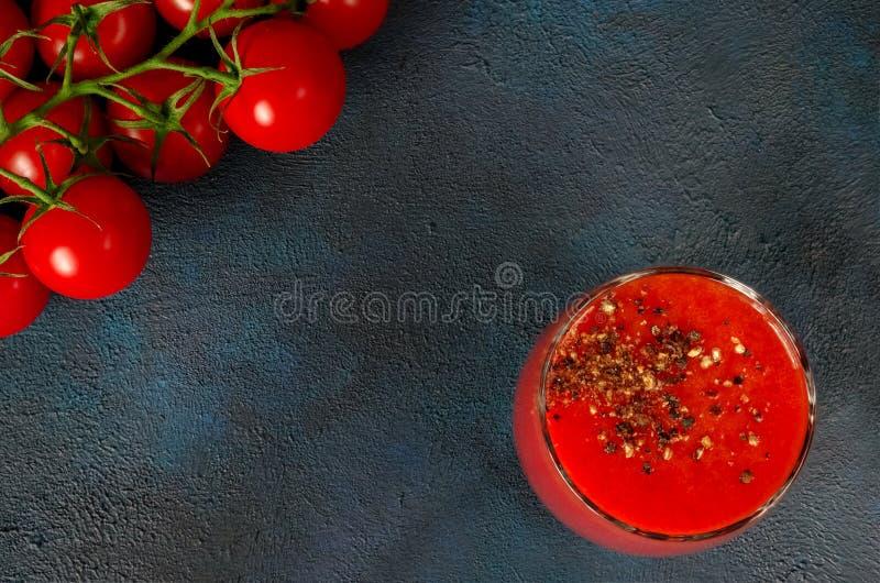 Tazza di vetro con il succo di pomodoro con pepe nero ed i pomodori ciliegia a terra su fondo scuro Vista superiore immagini stock