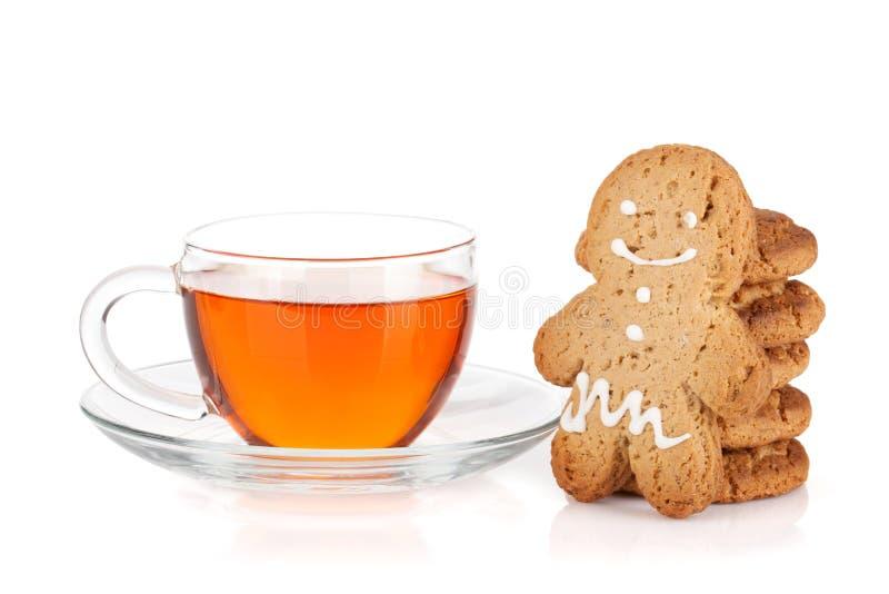 Tazza di vetro di tè nero con i biscotti e l'uomo di pan di zenzero casalinghi immagini stock libere da diritti