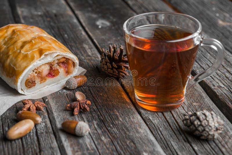 Tazza di vetro di tè, dello strudel alle mele e delle ghiande immagine stock libera da diritti