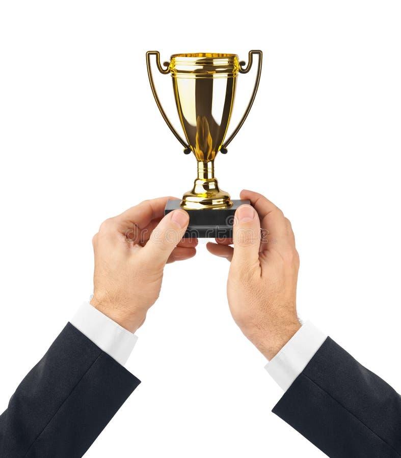 Tazza dorata del trofeo in mani fotografia stock libera da diritti