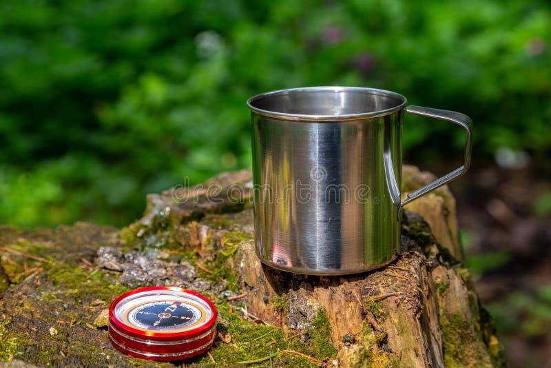 Tazza e bussola d'acciaio turistiche nella foresta di estate fotografie stock
