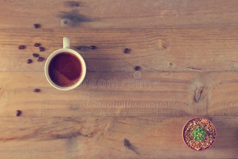 Tazza e cactus di caffè in vaso su di legno fotografia stock