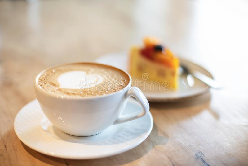 Tazza e dessert bianchi del cappuccino su fondo di legno marrone chiaro immagine stock libera da diritti