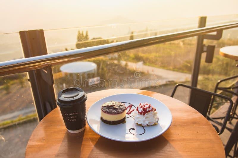 Tazza e dolce di caffè caldi sulla tavola con luce solare alla mattina thailand immagine stock libera da diritti