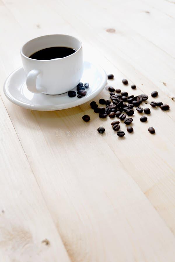 Tazza e fagioli di caffè sulla tavola immagini stock